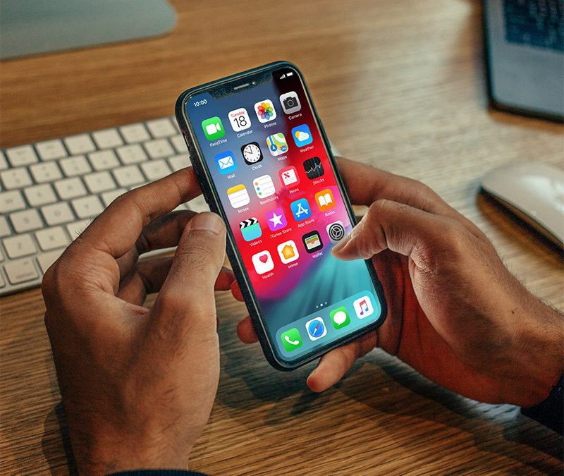 man holding iphone while sitting at his desk
