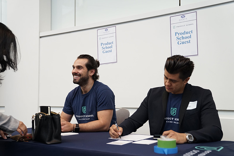 product school reps sitting at a table during a career fair